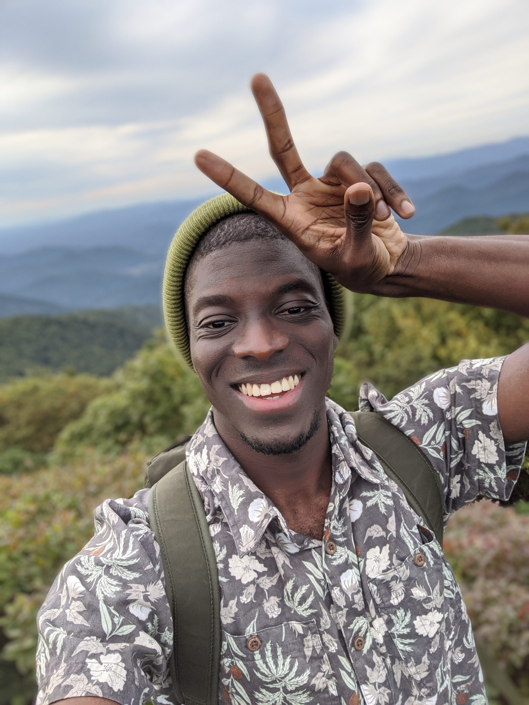 Amath Diouf throwing a peace sign on a hike.