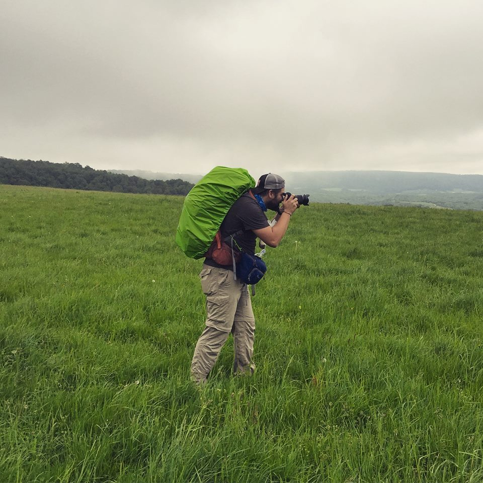 Man with a backpack on in a grassy field taking a picture