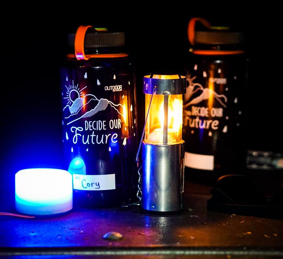 """Two Nalgenes with the words """"Decide Our Future"""" on them and lanterns on table at night"""