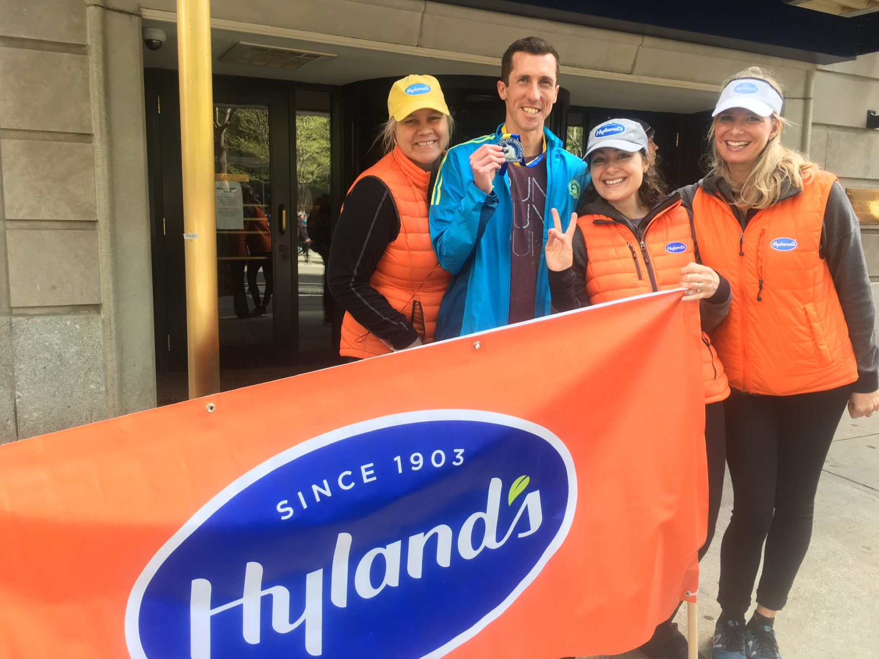 """3 women and a man with a Boston marathon medal standing behind an orange banner that reads """"Hyland's"""""""