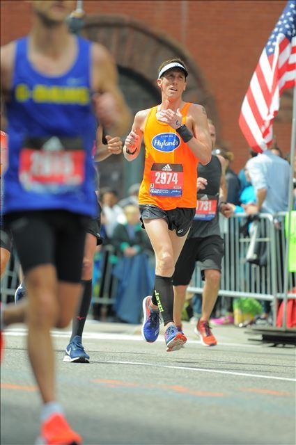 Man running in road race with orange Hyland's jersey on