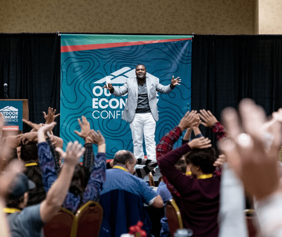 Man in blazer with hands in the air on stage in front of sign that reads Outdoor Economy Conference