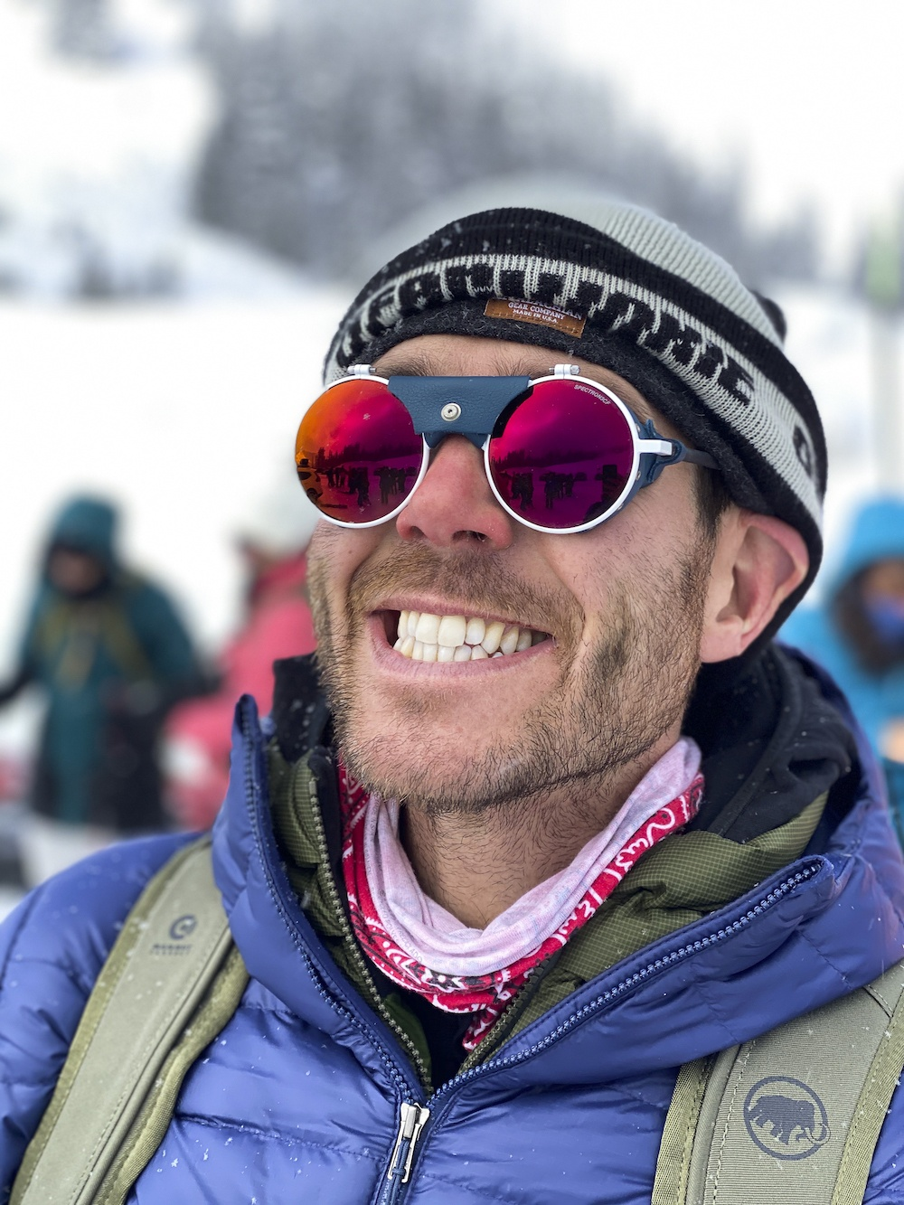 Man with scruffy beard, beanie, and glacier glasses on smiling big with snow in background.