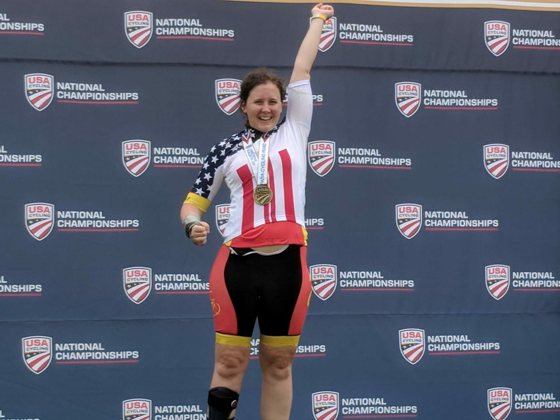 Woman with a medal around her neck and hand raised in the air at the USA Cycling National Championships