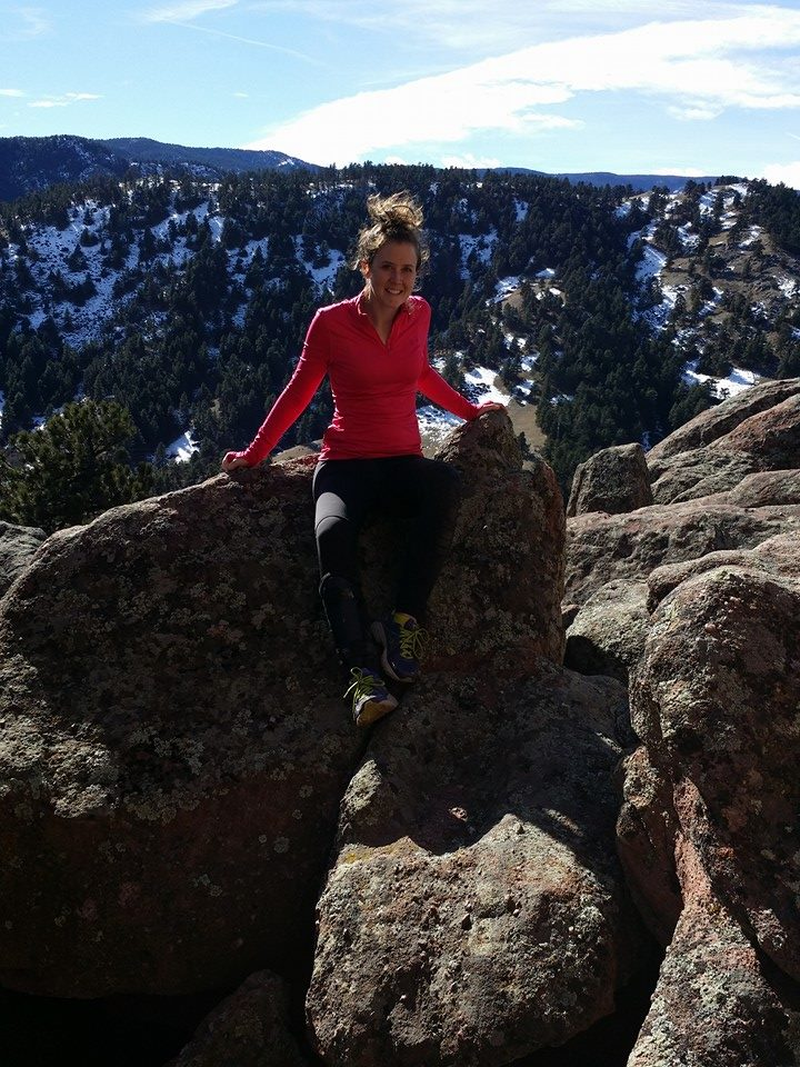 Woman sitting on rocky outcropping in Colorado mountains