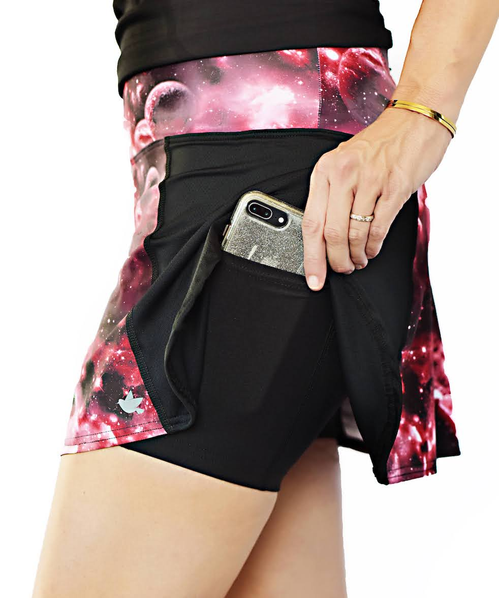 Woman wearing a black and pink performance skort, while tucking her phone into her pocket.