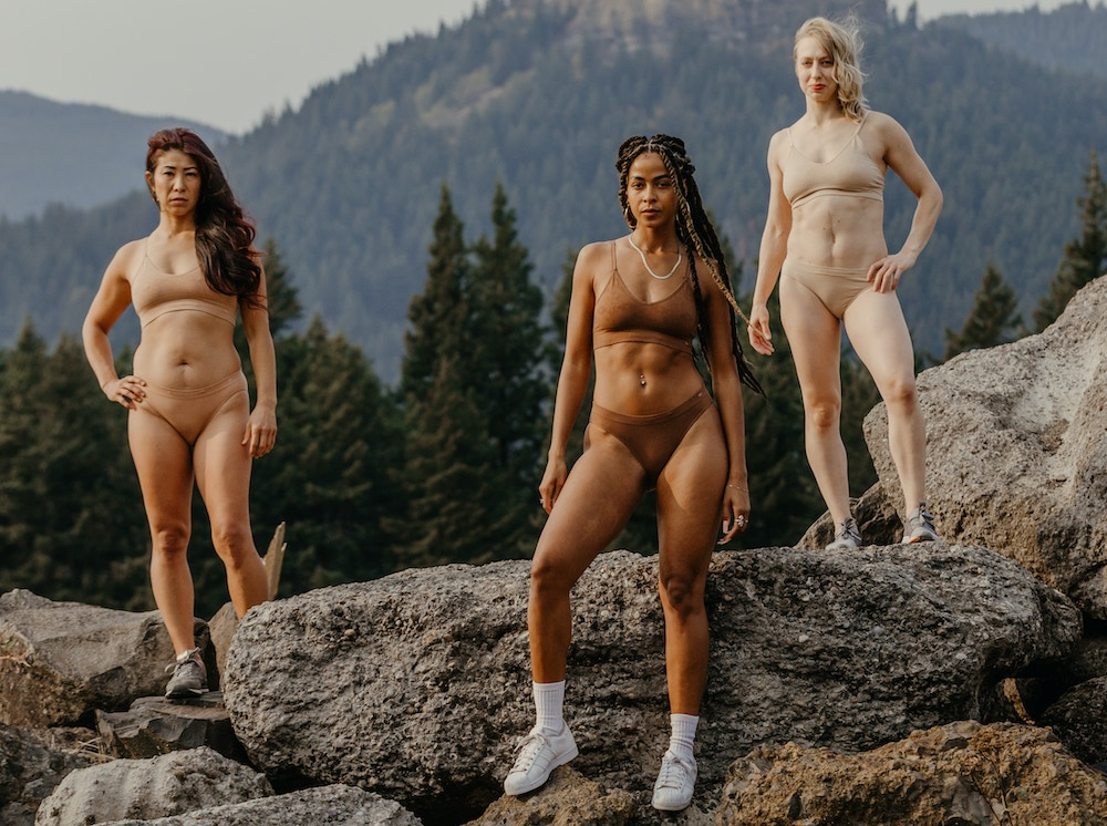3 women in their underwear and shoes standing on a rock with mountains behind them
