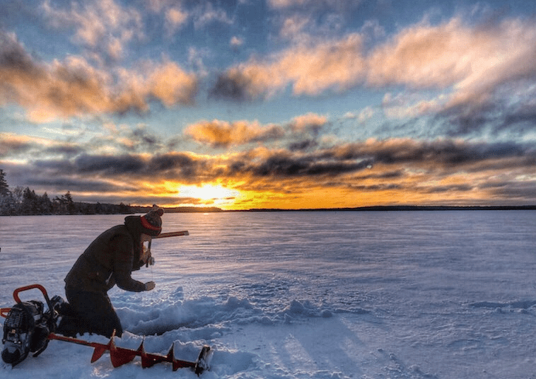 Woman dropping a line in the ice on a frozen lake with an auger next to her and a sunrise in the distance.