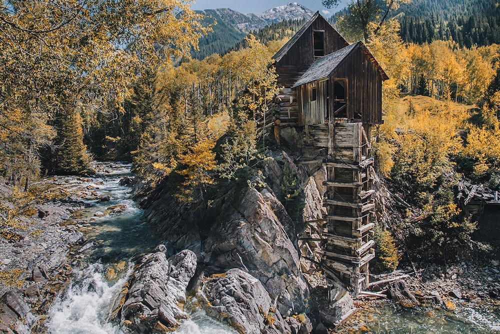 An old wooden mill set next to a gushing river with yellow Aspen trees in the backgound and snowy mountain peaks in the distance.