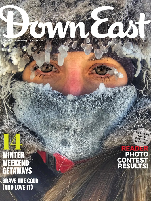 Down East Magazine cover with picture of woman with ice on her eyelashes, hair and hood. She has a fleece neck gaiter pulled up over her mouth and nose and it's covered in ice and frost.