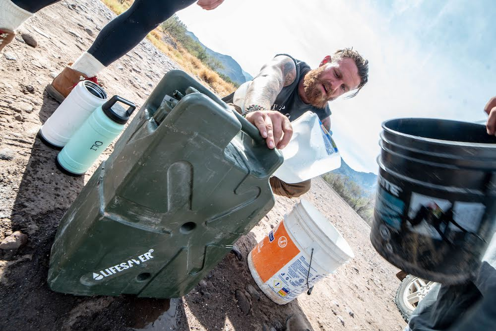 Man with beard in the outdoors funneling dirty water into a Lifesaver Jerrycan to filter.