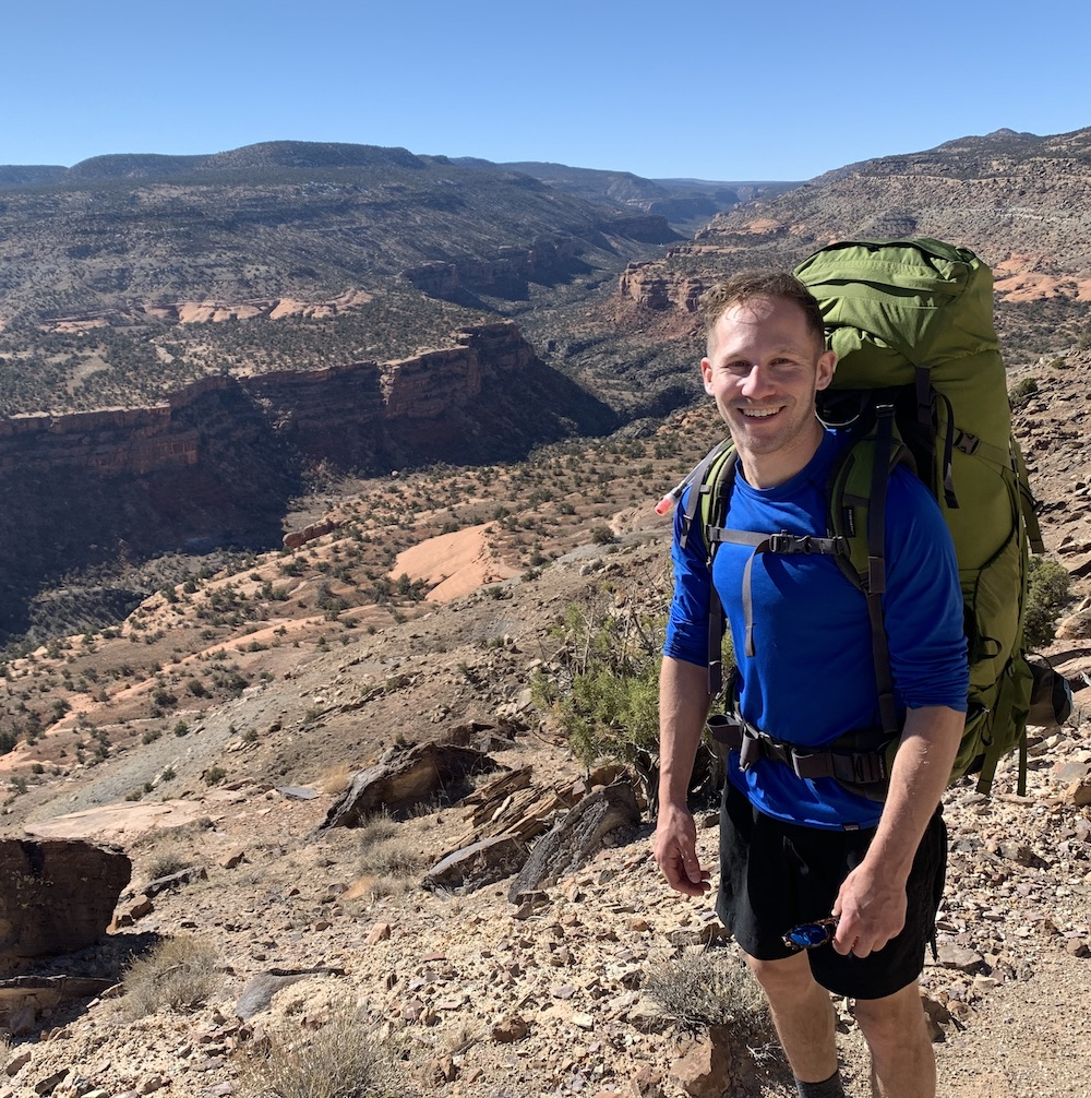 Man smiling at the camera while backpacking in the desert