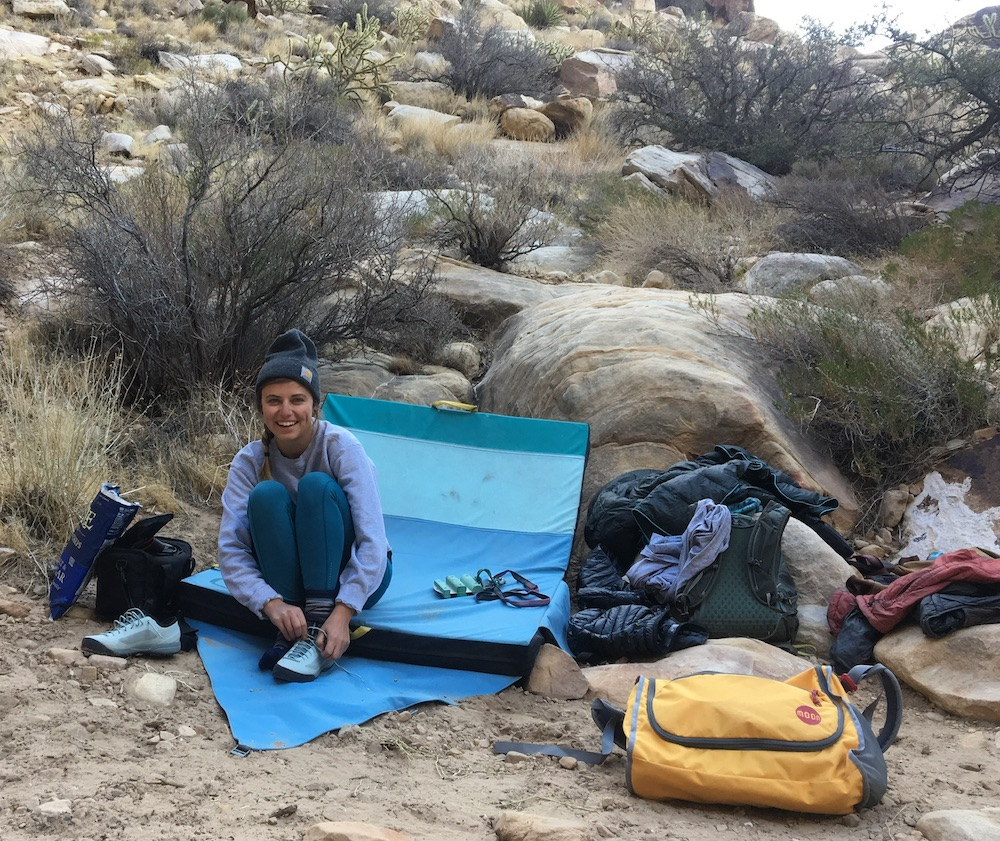 Woman with beanie on lacing up her shoes amongst cactus, sagebrush and bouldering mat and lots of bags and gear.