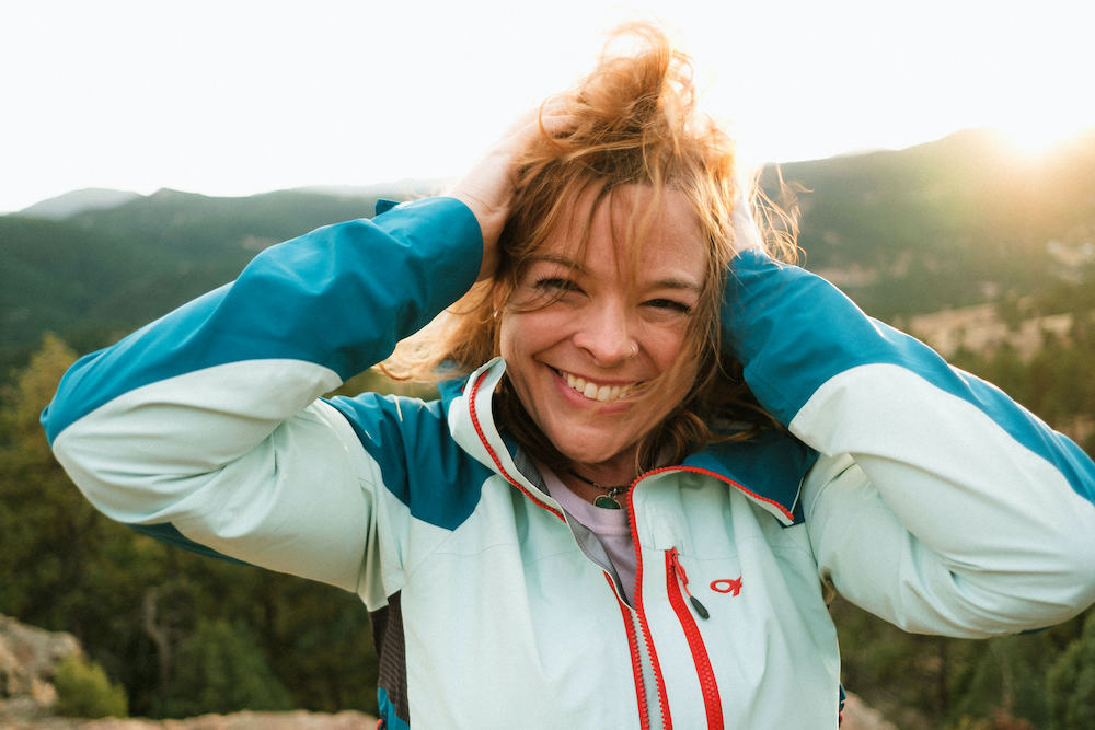Woman smiling on top of mountain with her hands in her hair.