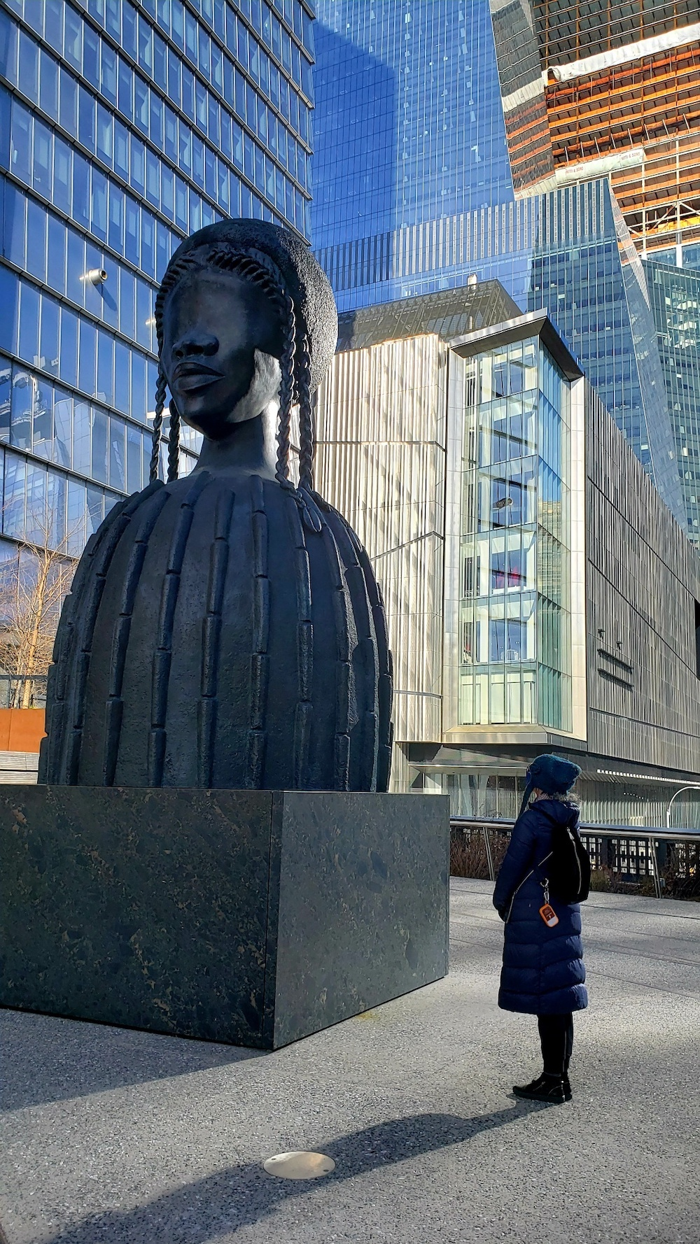 A woman in a winter coat standing and looking at an abstract statue of a black woman with braids.