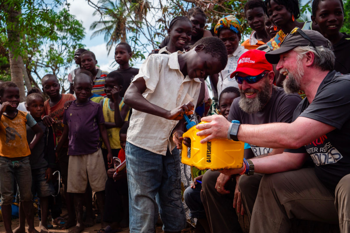 Men showing kids how to filter water using LifeSaver's products
