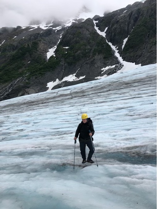 A woman with crampons and a helmet on using trekking poles on a glacier.