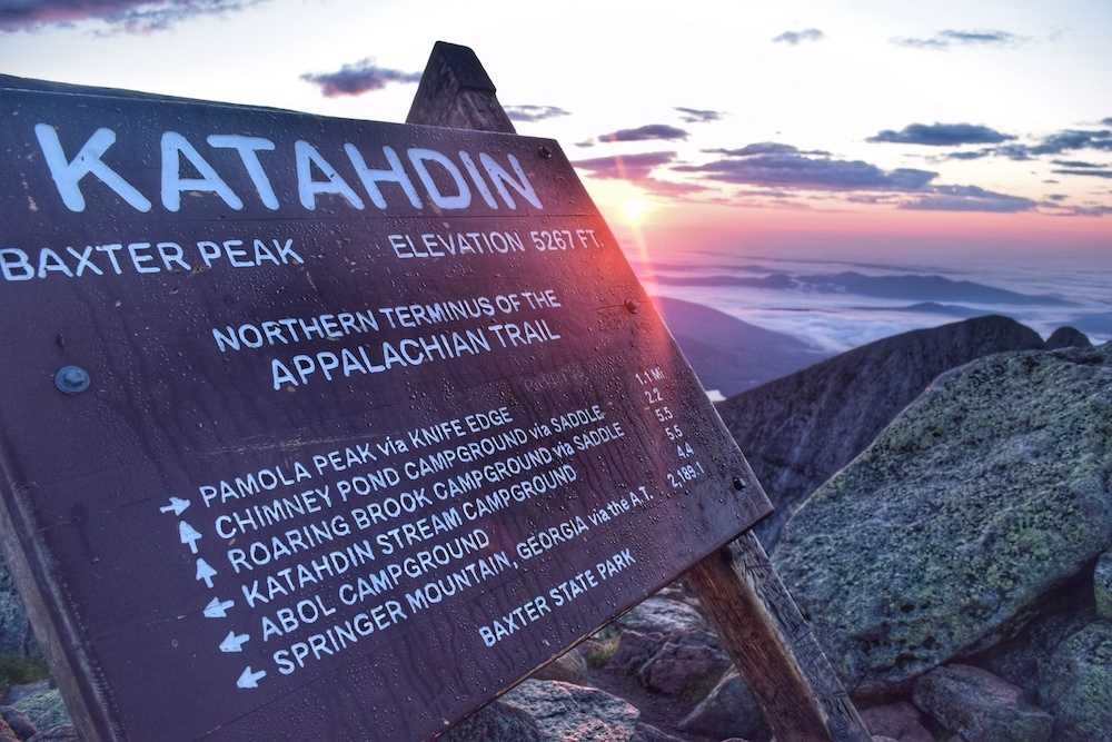 Image of a sign at the top of Mt Katahdin with rocks and clouds and mountains and a sunset in the background.