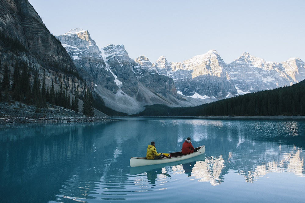 Two people in a canoe on a clear lake with snowy mountains in the background.