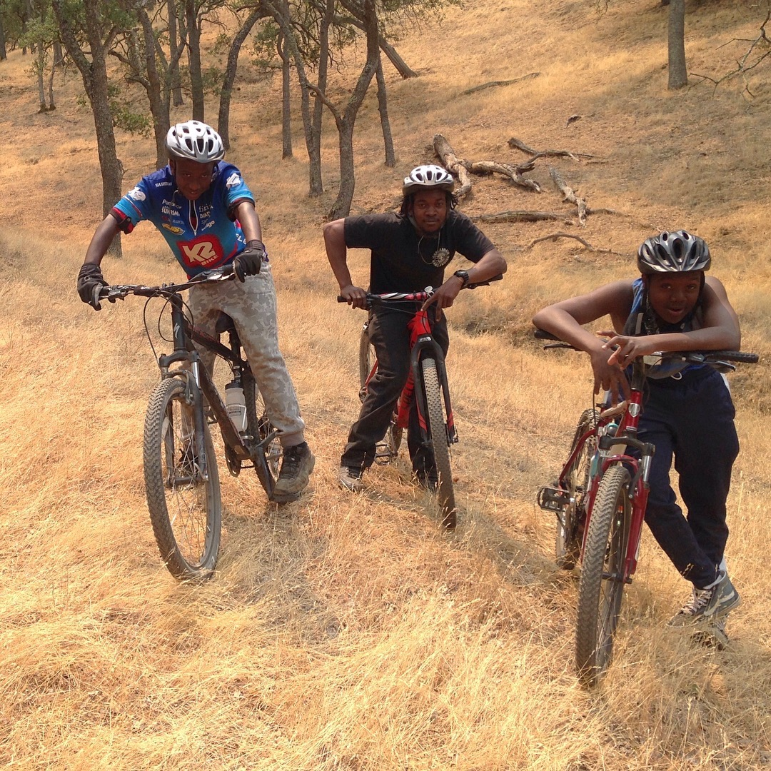 3 kids on bikes on a trail of golden grass