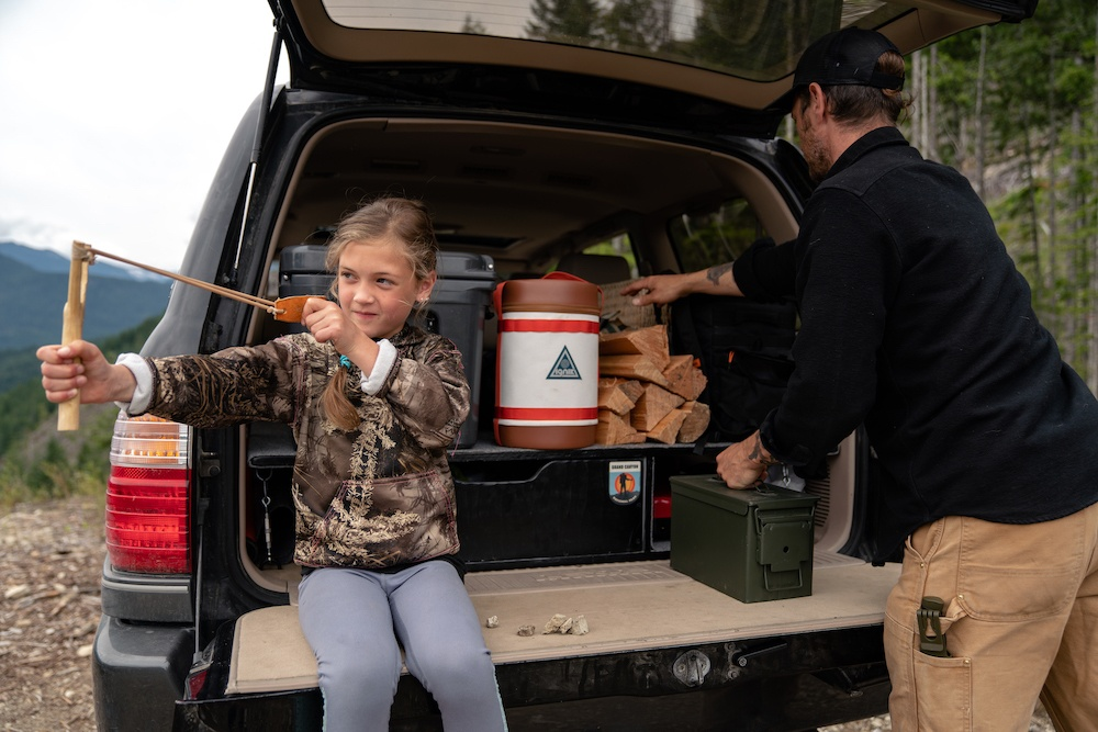 Man loading back of truck with wood and camping equipment while child sits on tailgate shooting a slingshot