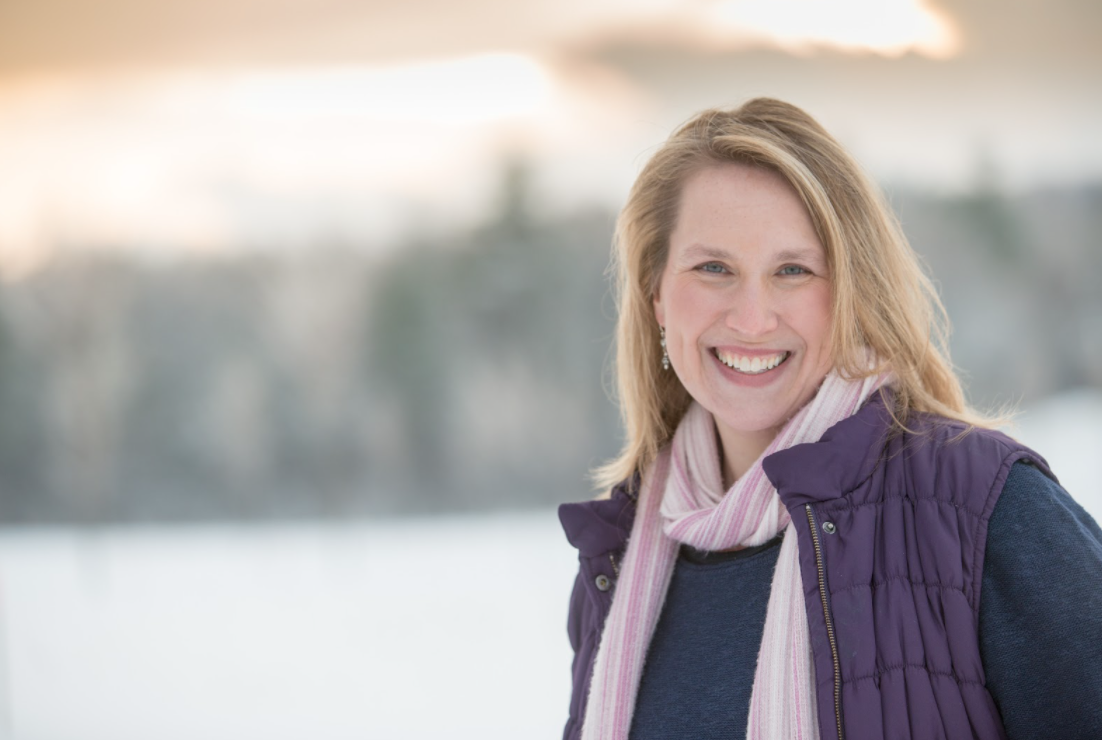 Kara Richardson Whitely with blond hair, a pink scarf, and a purple vest standing in front of a snowy background that is blurry and out of focus.