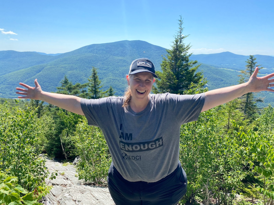 Kara Richardson Whitely standing on a mountaintop in Vermont with her arms stretched wide and smiling. Green trees and mountains in the background.