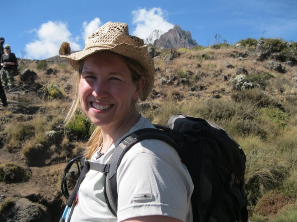 Kara Richardson Whitely wearing a straw hat with a backpack on and a tall mountain peak in the distant backgroud.