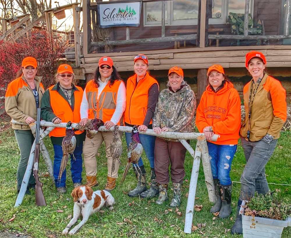Women wearing orange shirts standing behind horse hitch with pheasants they shot hanging over bar. Brittany spaniel is lying in front of the group.