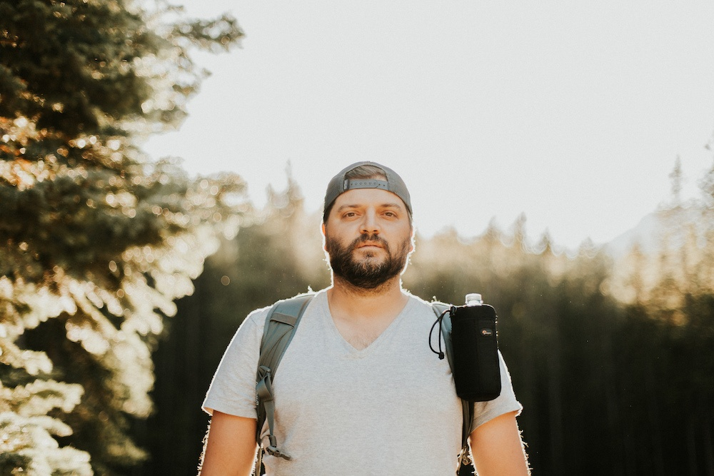Man with a hat on backward and a backpack on. Trees sunlit behind him.