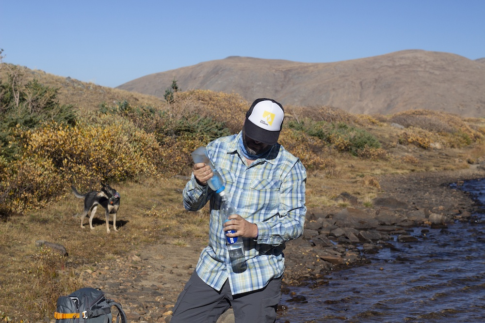 A man filtering water from a creek in the mountains with a dog in the background.