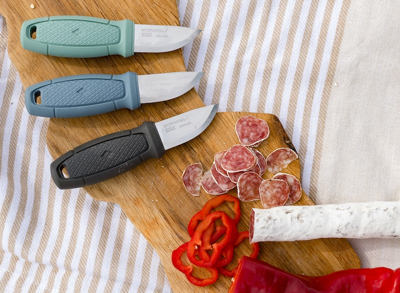 3 small hand knives in green, blue, and black on a cutting board with freshly cut salami and red pepper.