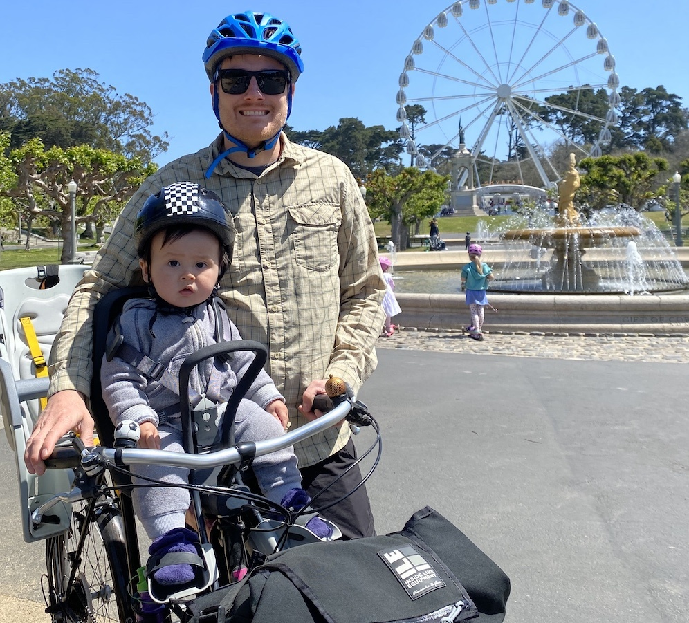 Man with baby on a bike in front of a water fountain and ferris wheel
