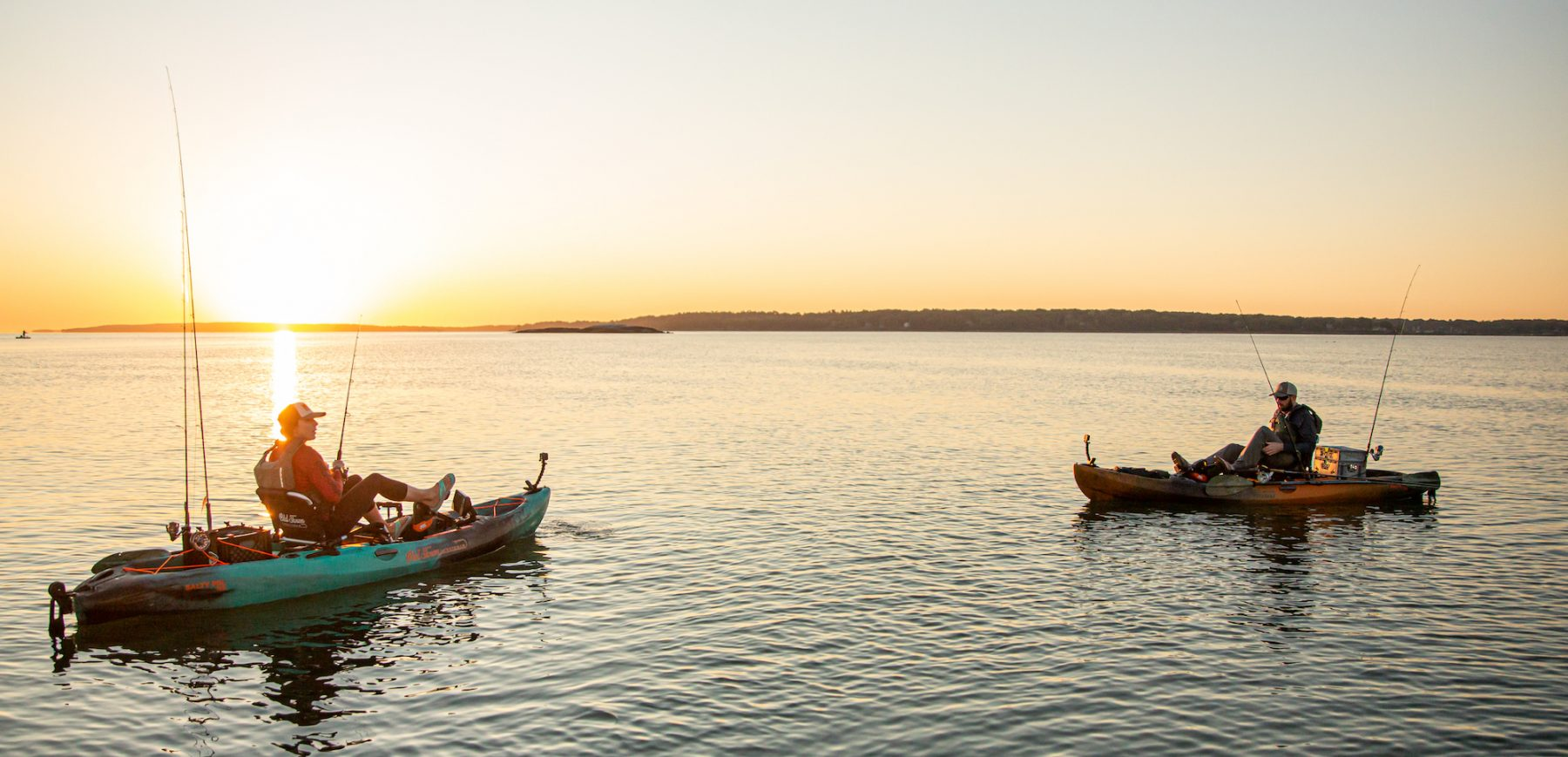A woman and man paddling sit on top kayaks and fishing with a sunset