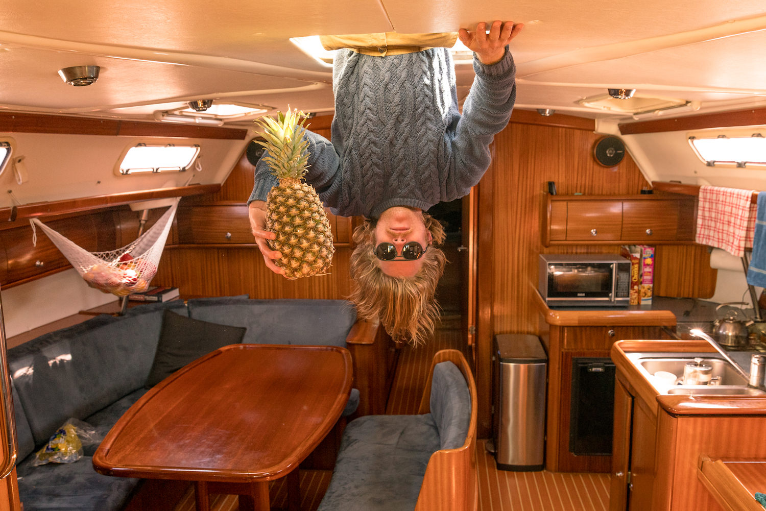 Man hanging upside down in the under deck of a boat and holding a pineapple.
