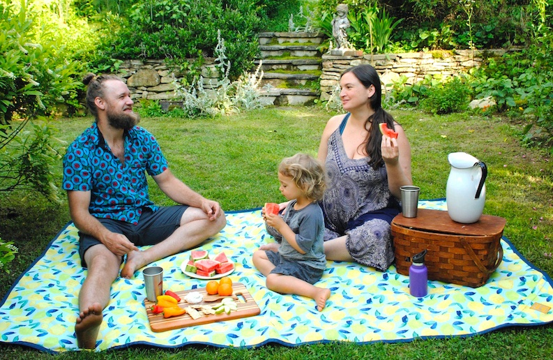 A family sitting on a Rugged Tarpestry