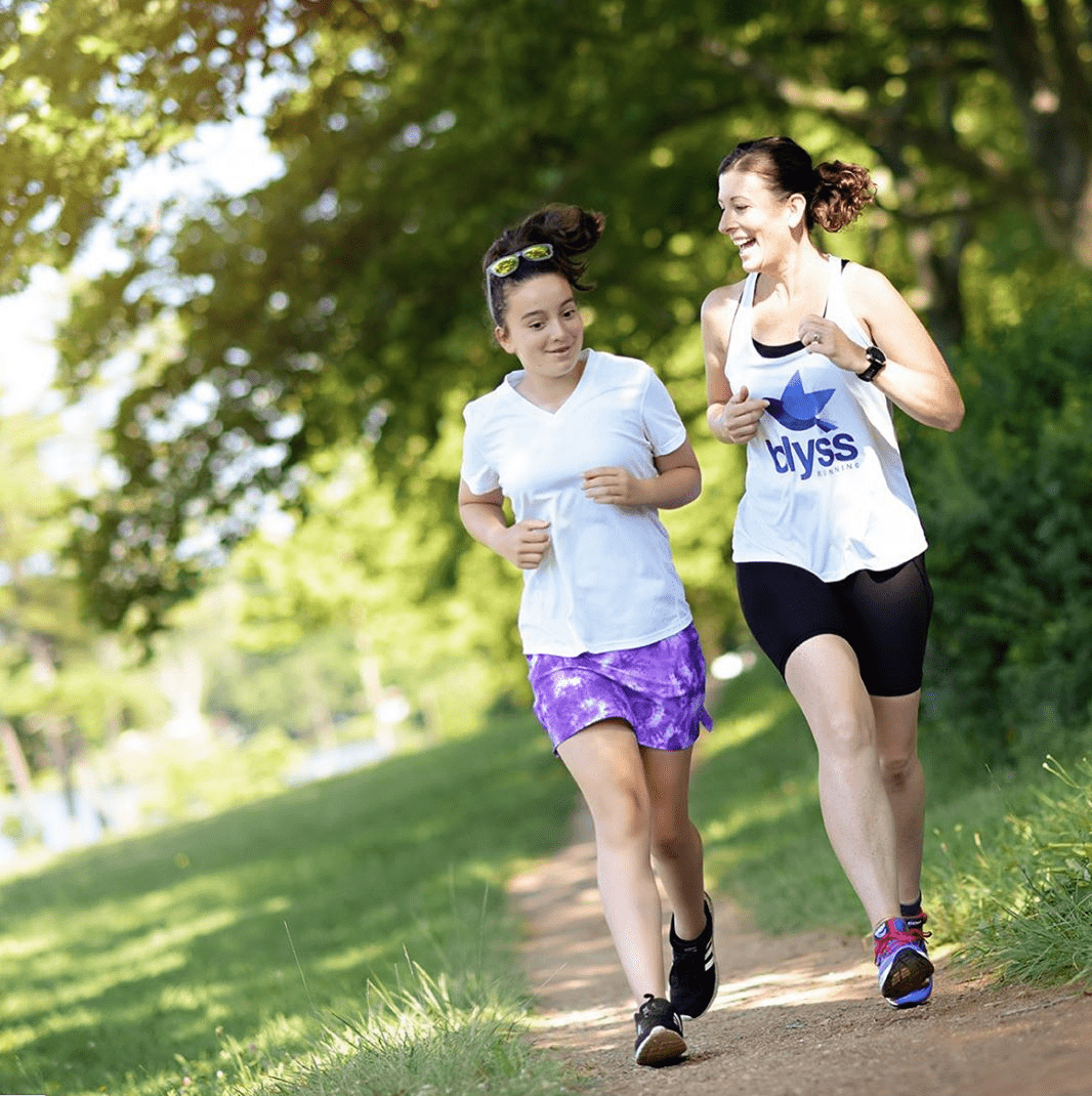 A mother and her teen daughter running down a dirt trail with green grass and blurry trees behind them. The mother's tee says Blyss with a bluebird on it.