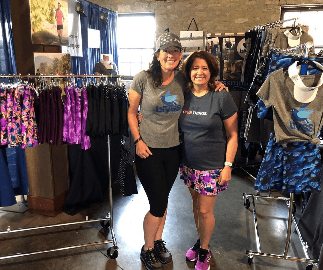 Two women with arms around each other posing for a picture in front of clothing displays for running skirts and tees.