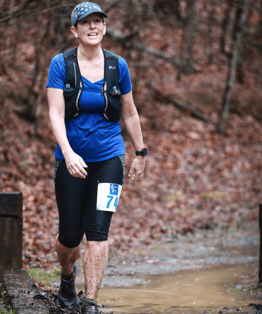 Woman at a muddy trail race in a blue shirt, grey hat and black capri pants.