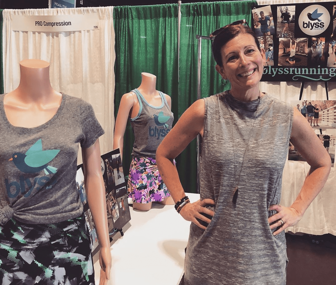Woman standing by two mannequins wearing tanks that say Blyss with bluebirds on them and running skirts
