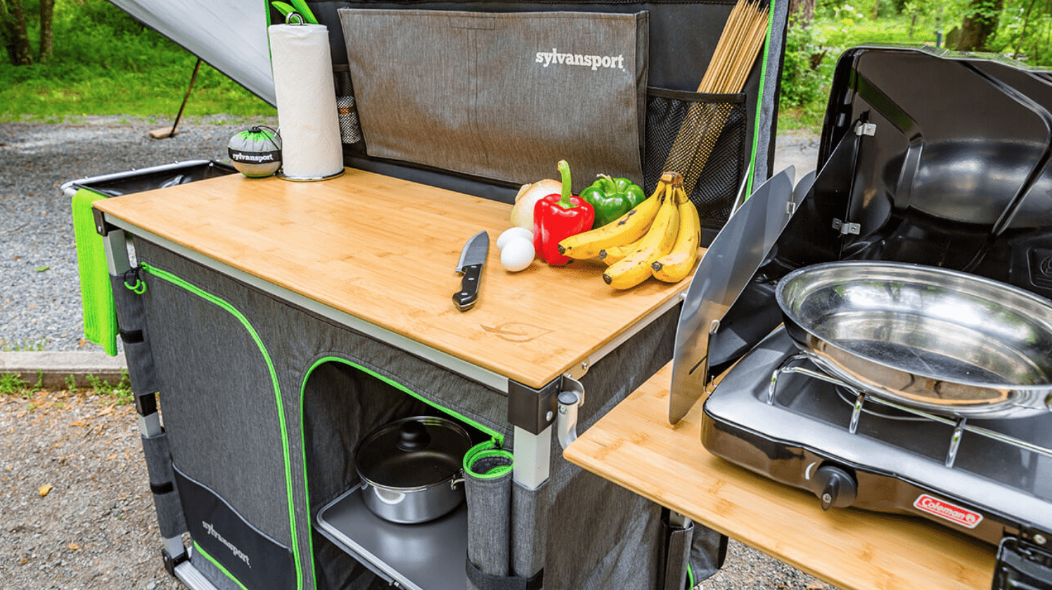 camp kitchen set up campside with bananas, peppers, knife and pan about to be used.