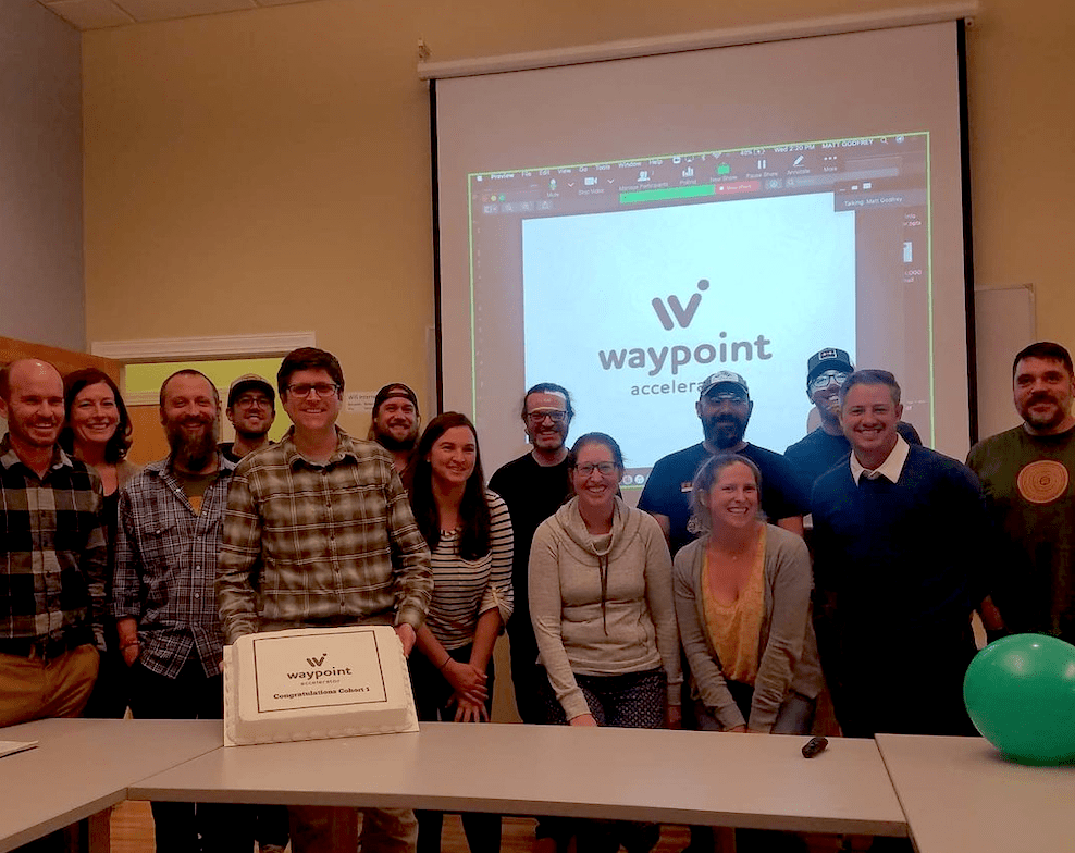 Group of people huddled together for a picture around a cake saying Waypoint Congratulations cohort 1. Dropdown projection screen behind them reading Waypoint Accelerator.