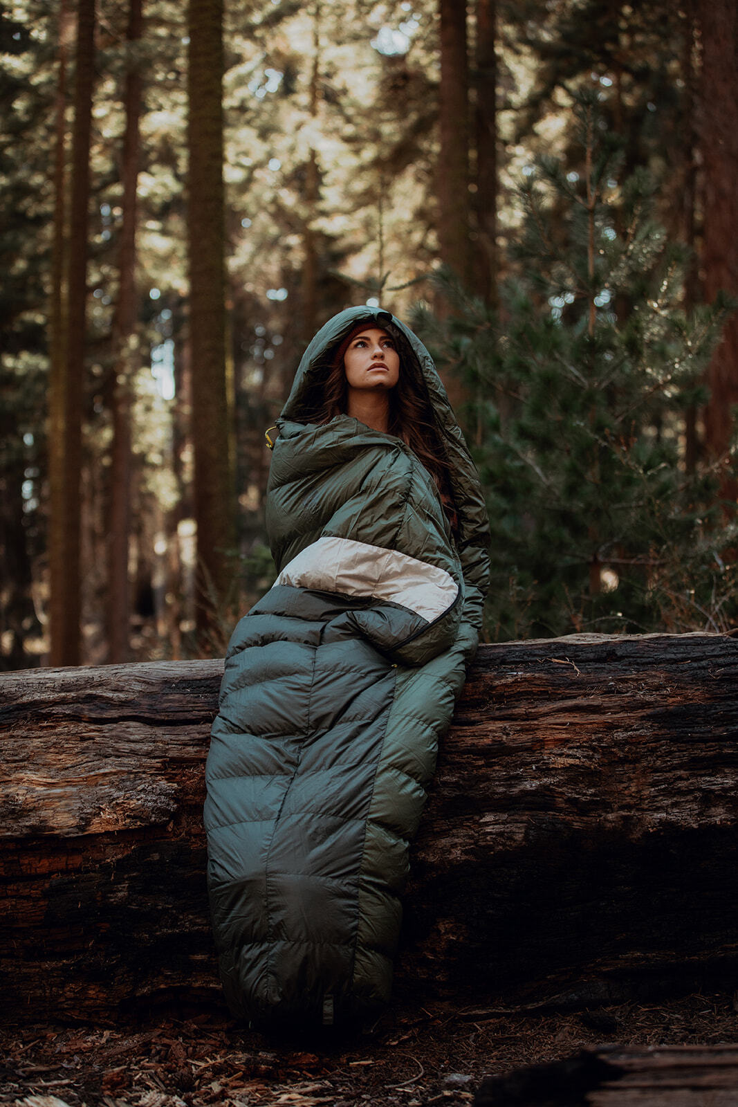 Woman snuggled in a sleeping bag while sitting on a log and staring up at the sky.