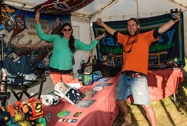Man and woman in booth at festival with blankets hanging on walls. Arms in the air celebrating.