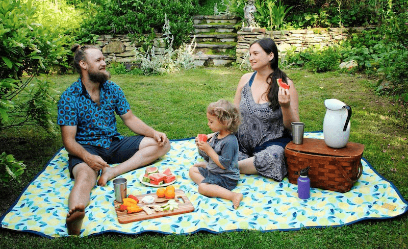 Family sitting on a picnic blanket (Tarpestry) with a small child eating watermelon.