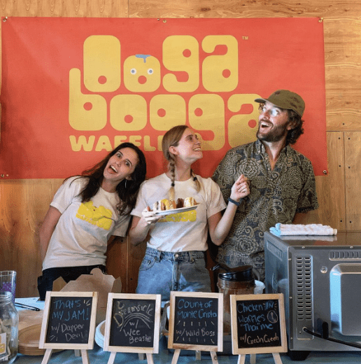 3 people who work for a small business standing in front of a sign that reads Ooga Booga Waffles and the woman in the middle is holding a plate of waffles.