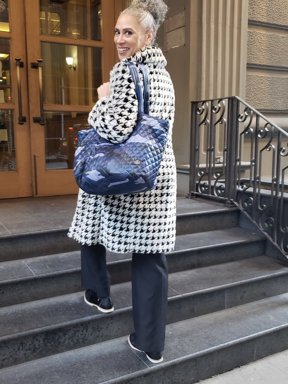 Woman walking up the steps of a building, wearing a black and white houndstooth faux fur coat, and looking back at the camera.