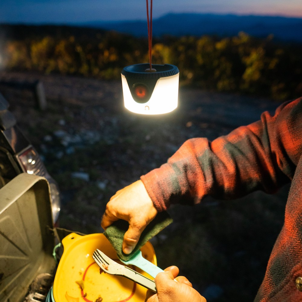 Man washing dishes campside with a lantern overhead.