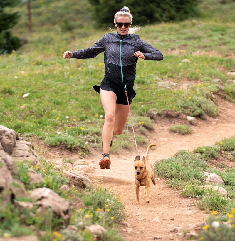 Woman running on a mountain trail with a dog tied to her waist and running in front of her.