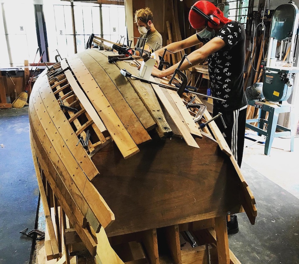 Youth working on a wooden boat build in a shop